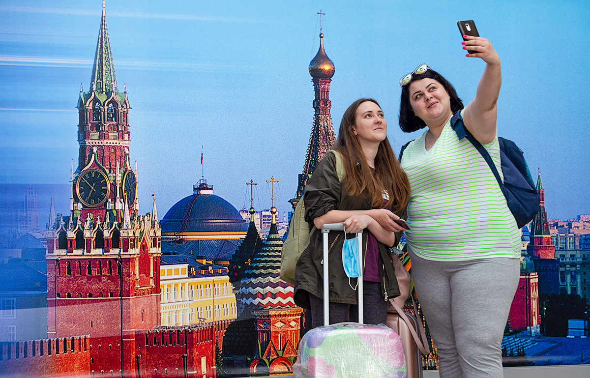 Passengers take a selfie at the Sheremetyevo International Airport in Moscow, Russia