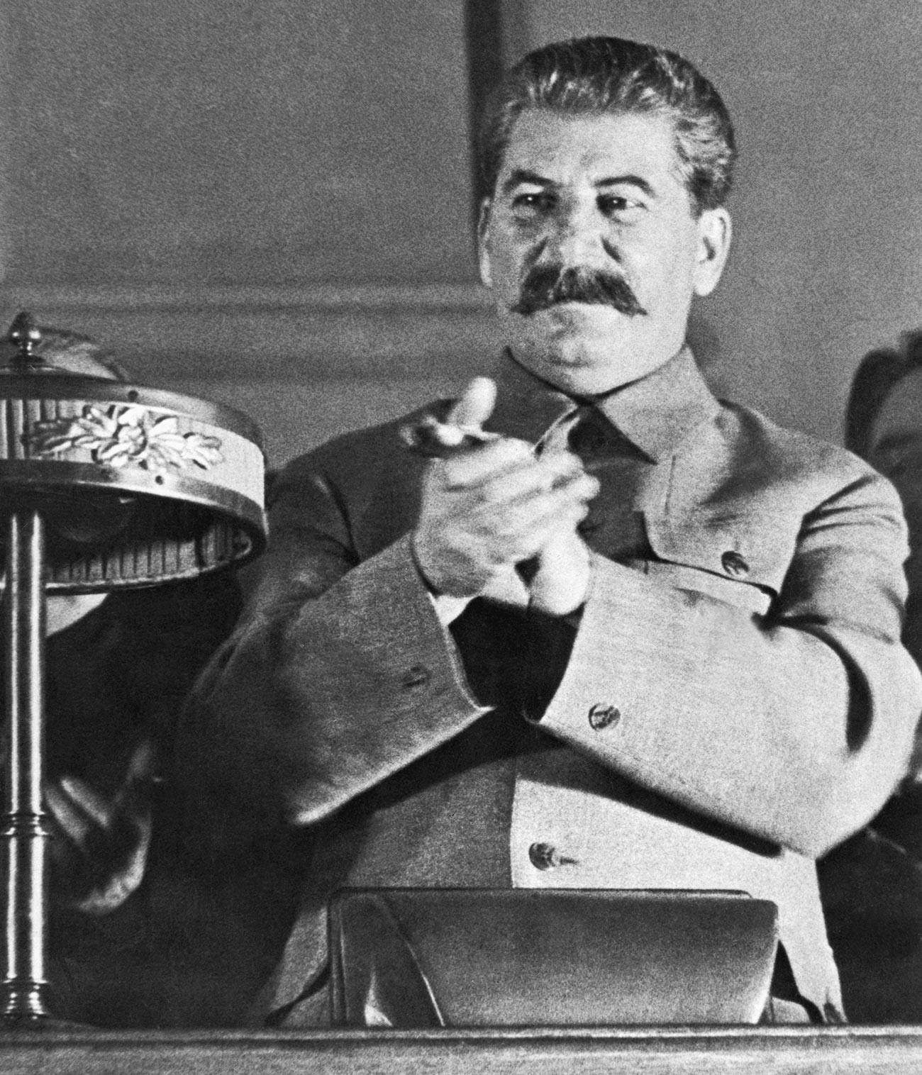 Stalin applaudiert einem Redner, der während des achten Sowjetkongresses über Stalins Bericht über den Entwurf der neuen Verfassung der UdSSR spricht.