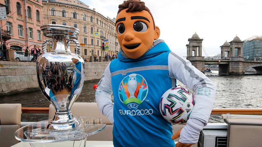 Maskota Evropskega prvenstva v nogometu 2020 Skillzy pozira s trofejo EURO 2020 med vožnjo z ladjo po reki Fontanki med uradno trofejno turnejo EURO 2020 v Sankt Peterburgu v Rusiji, v soboto, 22. maja 2021. Sankt Peterburg bo gostil sedem preloženih tekem iz EURO 2020, vključno s četrtfinalom.