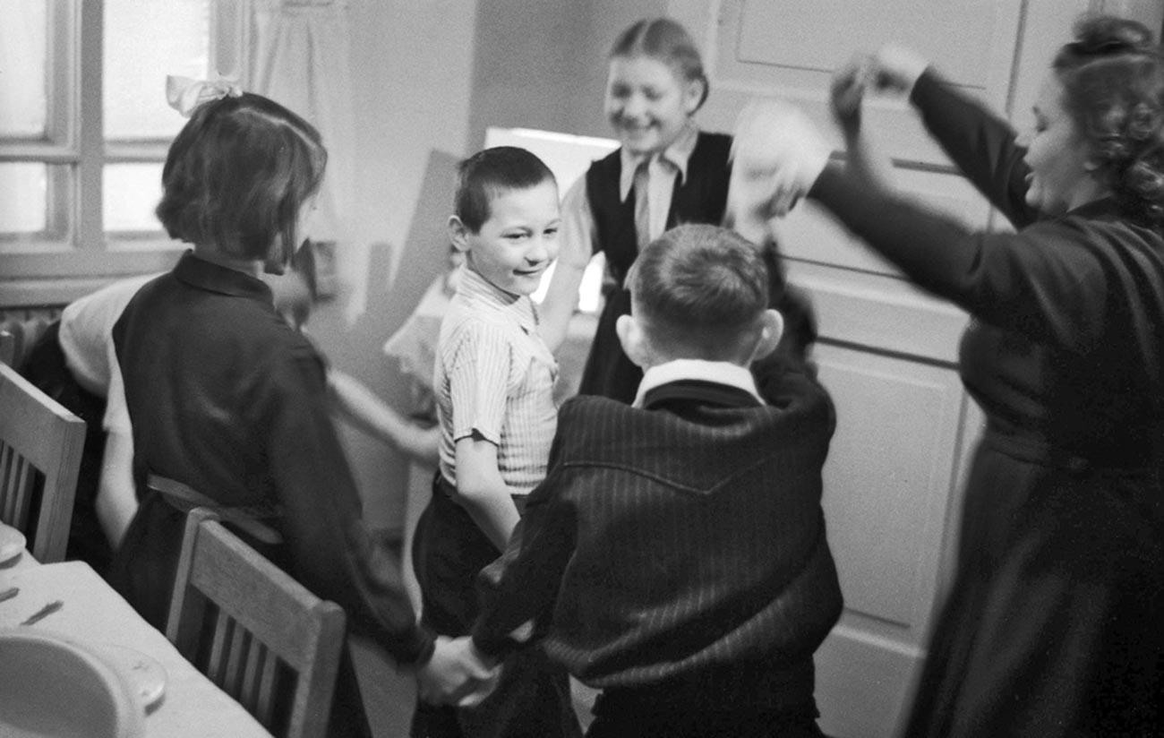 Crianças felicitam colega de classe por aniversário.