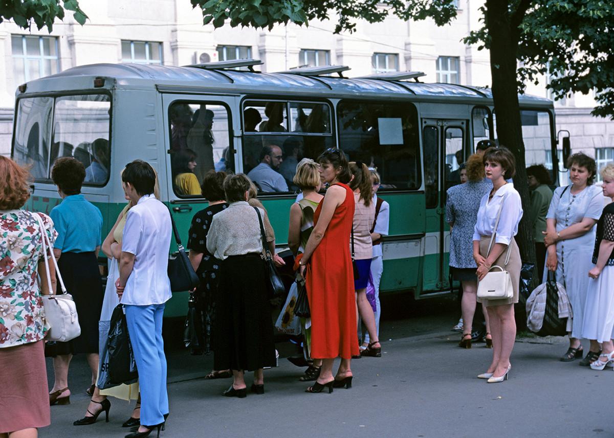 Leute an einer Bushaltestelle.