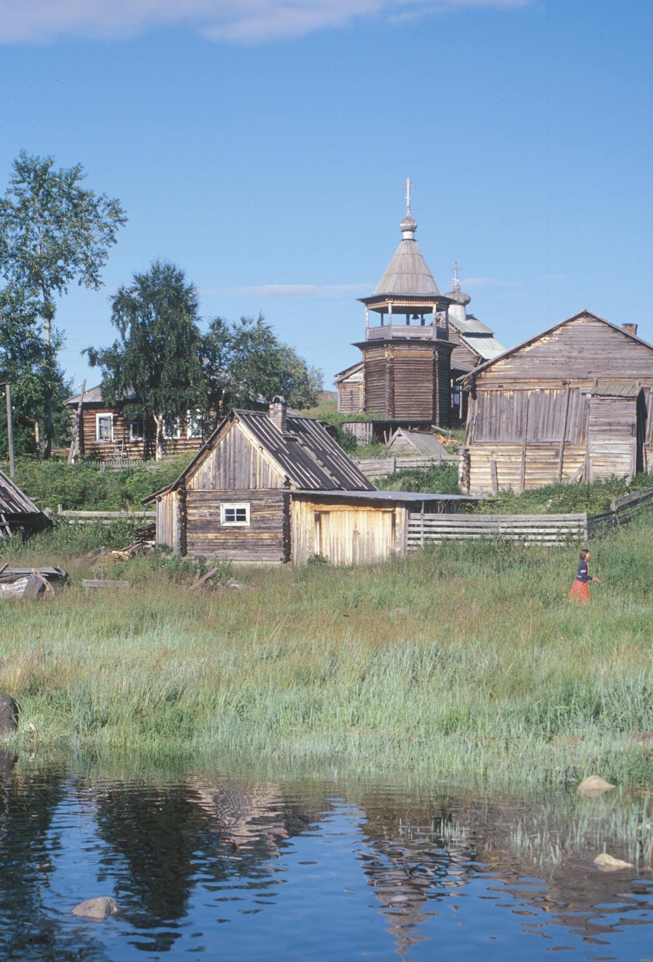 コヴダ村。丸太小屋と蒸し風呂と納屋。背景は聖ニコライ教会と鐘楼。2001年7月24日。