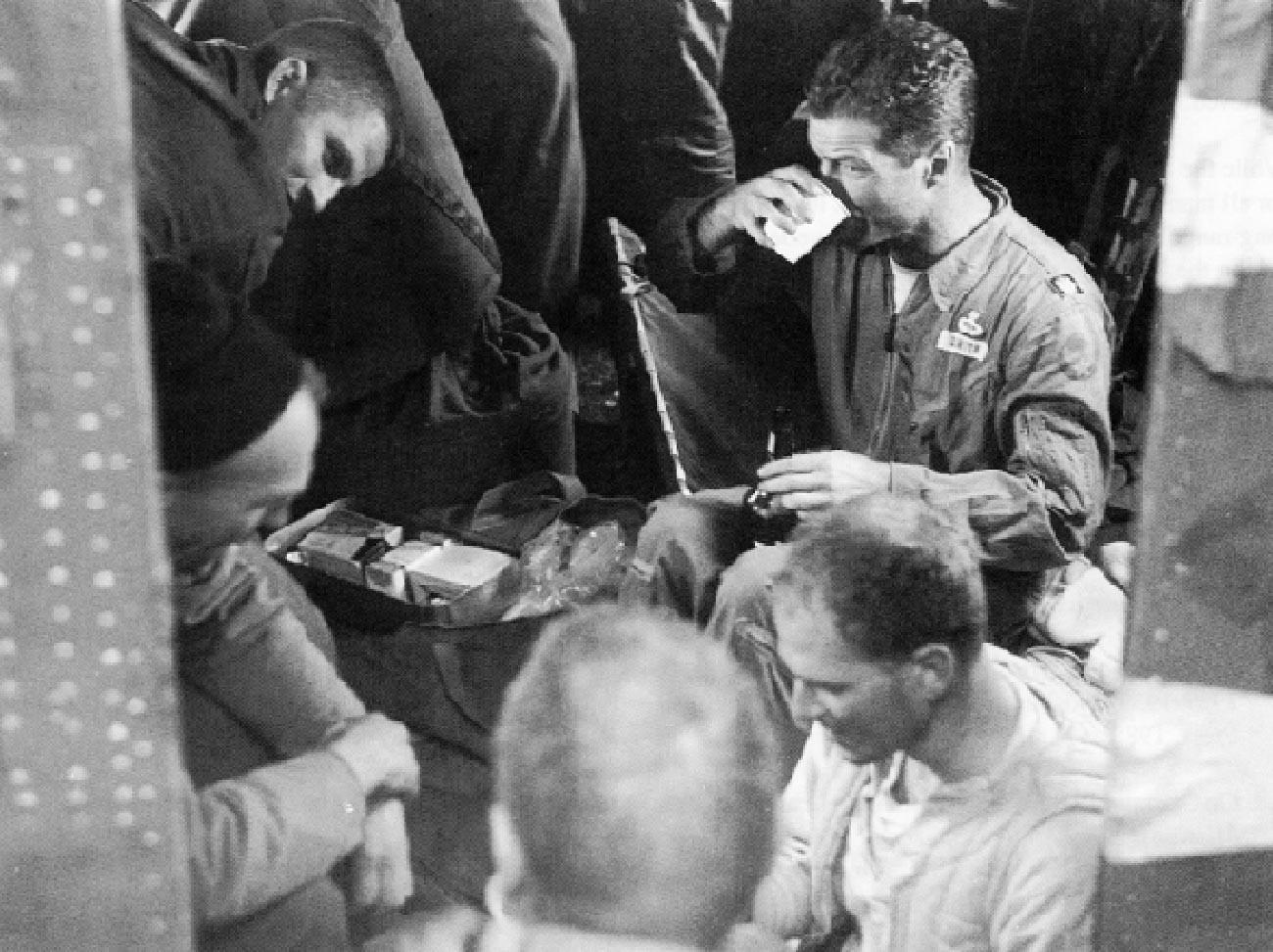 Participants à l'opération après l'ascension réussie des experts à bord du B-17: le major Smith (avec une tasse) prenant une portion de