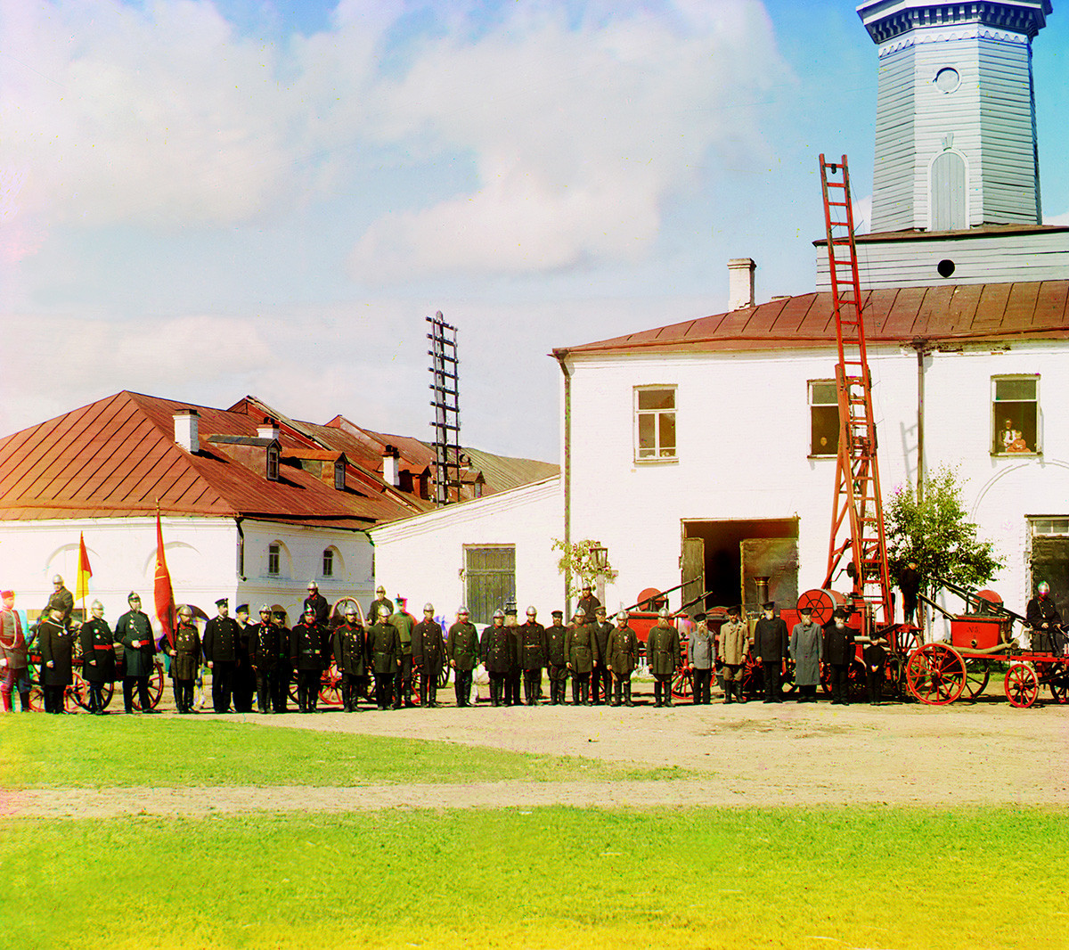 Fire station & watchtower with members of fire brigade & local administration. Left: partial view of Trading Rows. Summer 1909