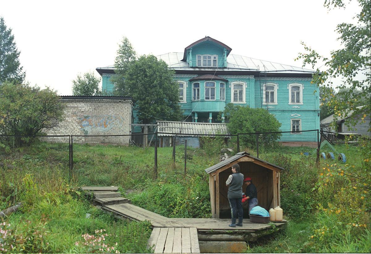Hiša E. I. Matvejeve (danes vrtec), ulica Ciurupa (nekdanja Plemiška) 41. Fasada s pogledom na potok Vjangi. V ospredju: lesena lopa nad izvirom. 28. avgust 2006