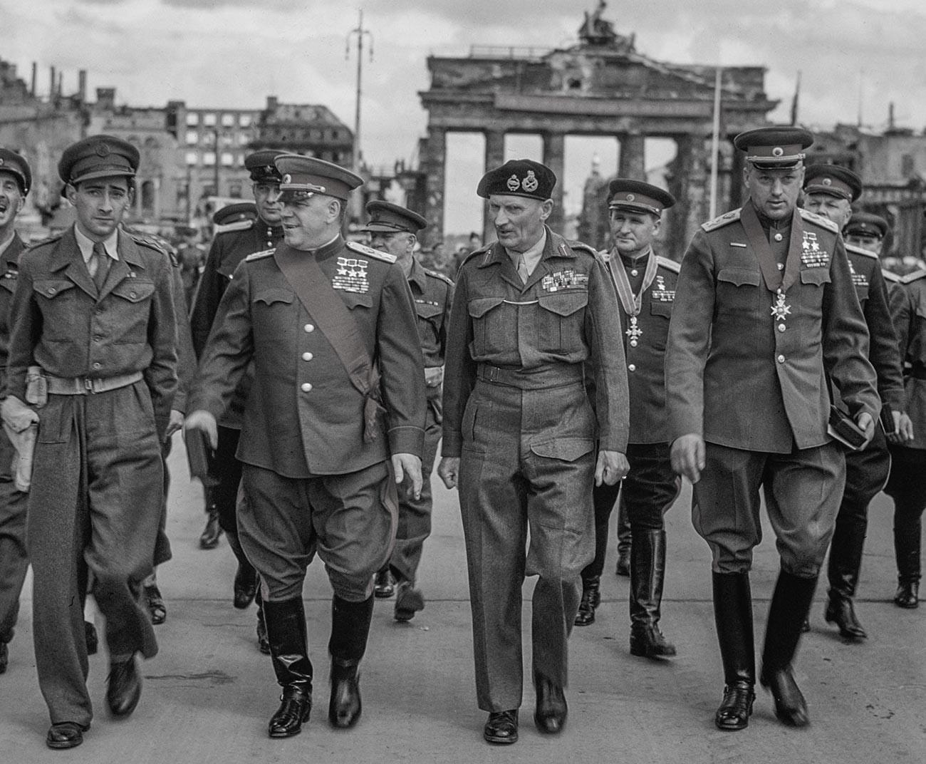 L'adjoint au commandant suprême de l'Armée rouge, maréchal Gueorgui Joukov, le commandant du 21e groupe d'armées field marshal Bernard Montgomery, le maréchal Constantin Rokossovski et le général Sokolovski quittent la porte de Brandebourg après une cérémonie.