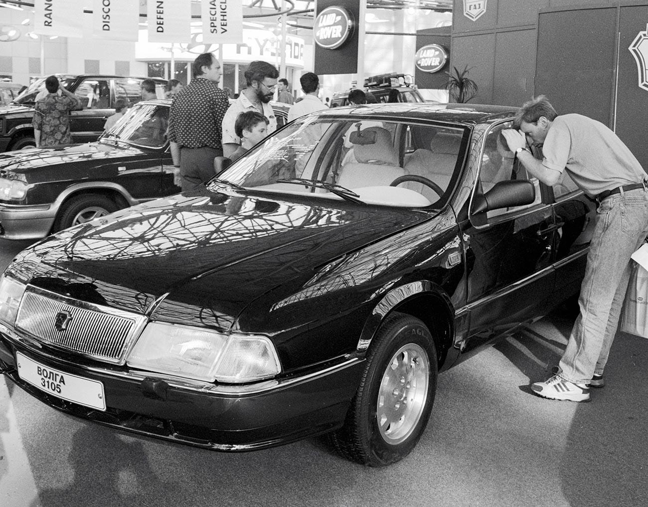 """Посетители на Меѓународниот саем на автомобили 1995 година разгледуваат автомобил ГАЗ-3105 """"Волга""""."""
