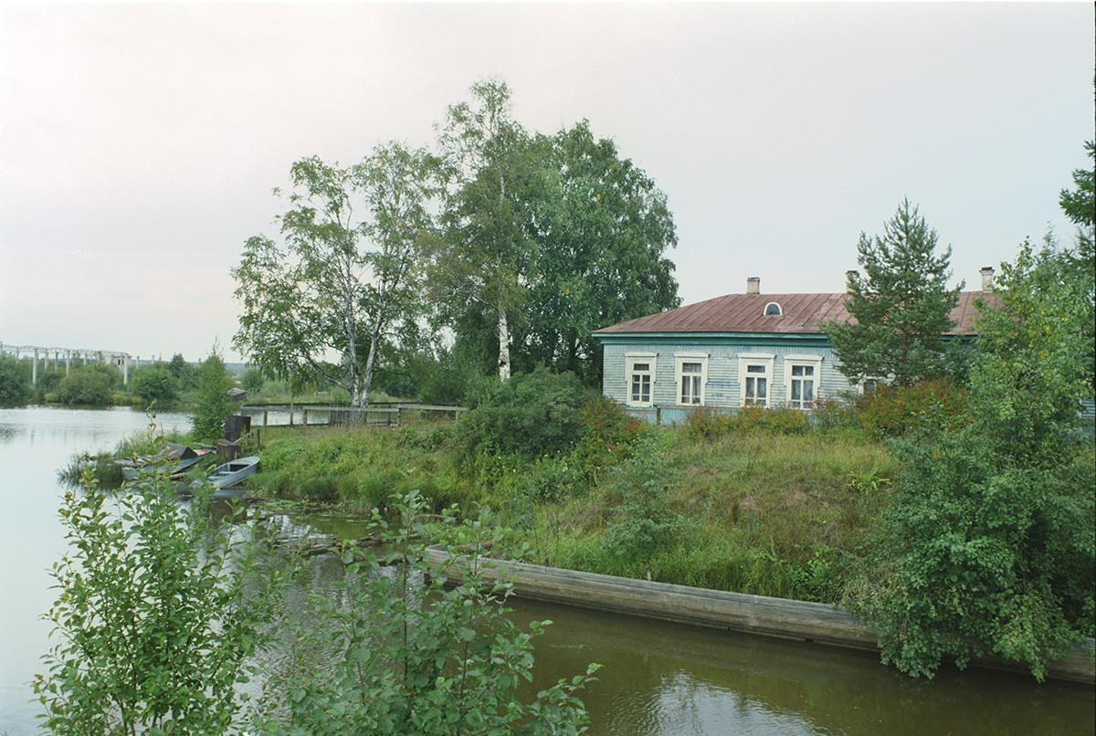 Rivière Vytegra avec les vestiges du canal Mariinsk à l'écluse de Saint-Serge. Arrière-plan: bâtiment en bois du XIXe siècle. 28 août 2006