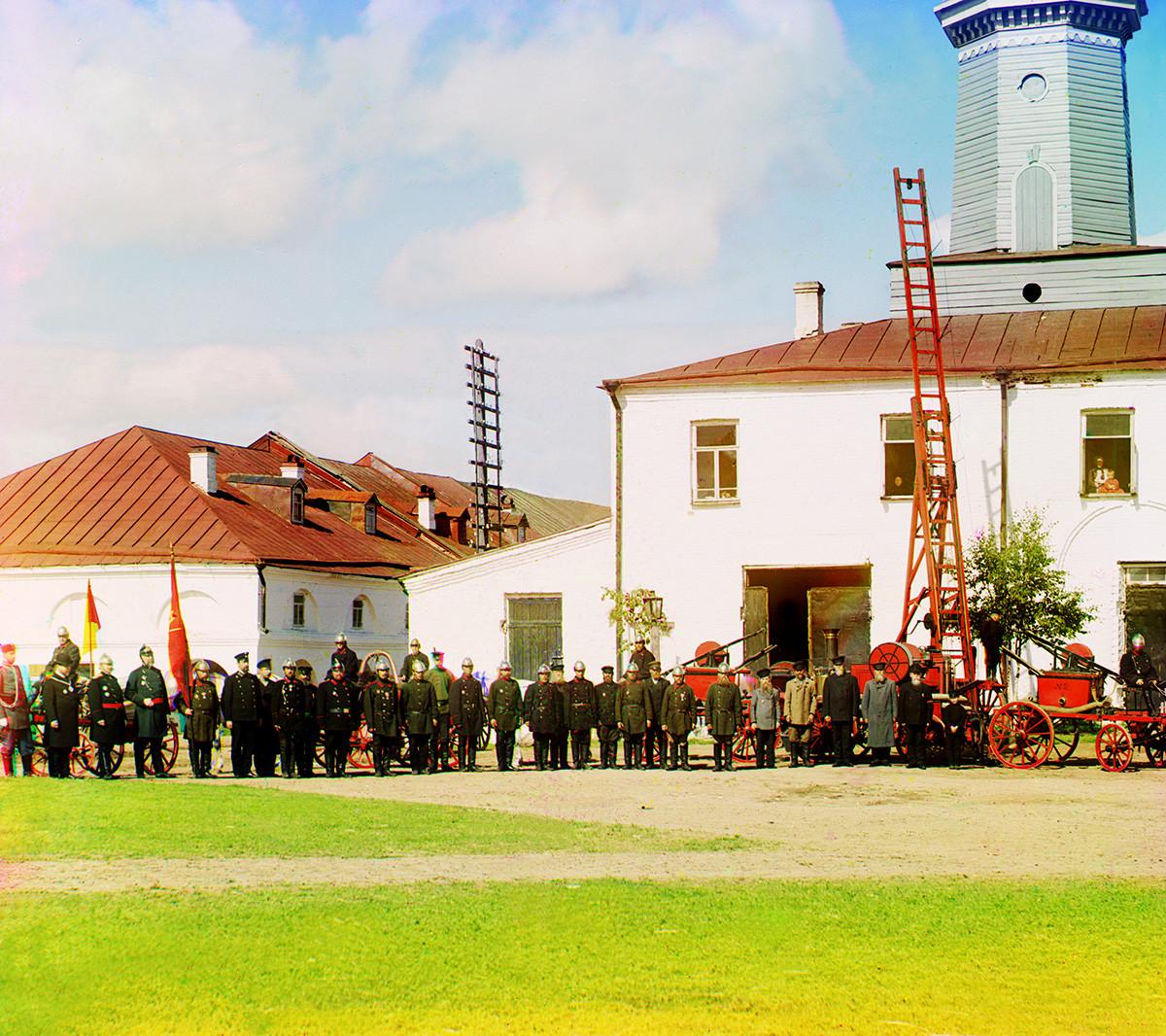 Caserne de pompiers et tour de guet avec des membres des pompiers et de l'administration locale. À gauche : vue partielle des galeries commerciales. Été 1909