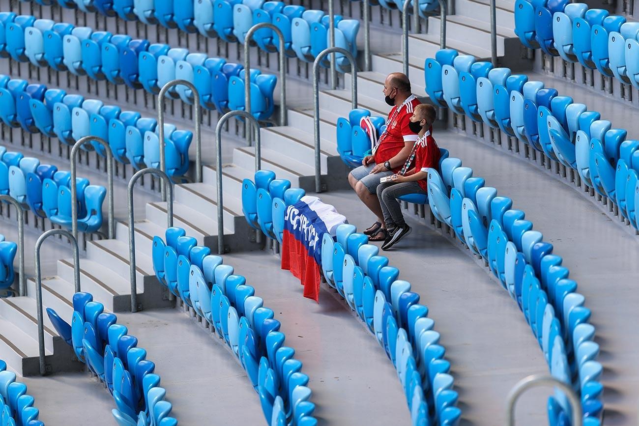 """Руски навијачи са маскама на лицу чекају на својим местима пре утакмице другог кола групе Б Европског фудбалског првенства 2020. између Финске и Русије на стадиону """"Санкт Петербург"""" 16. јуна 2021. у Санкт Петербургу у Русији."""
