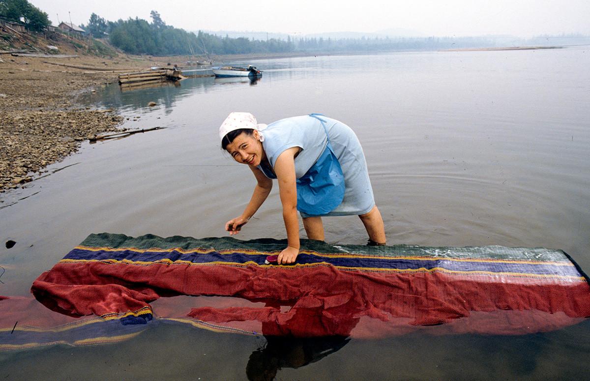 Жительница во время стирки ковровой дорожки на реке Бирюса, Красноярский край.