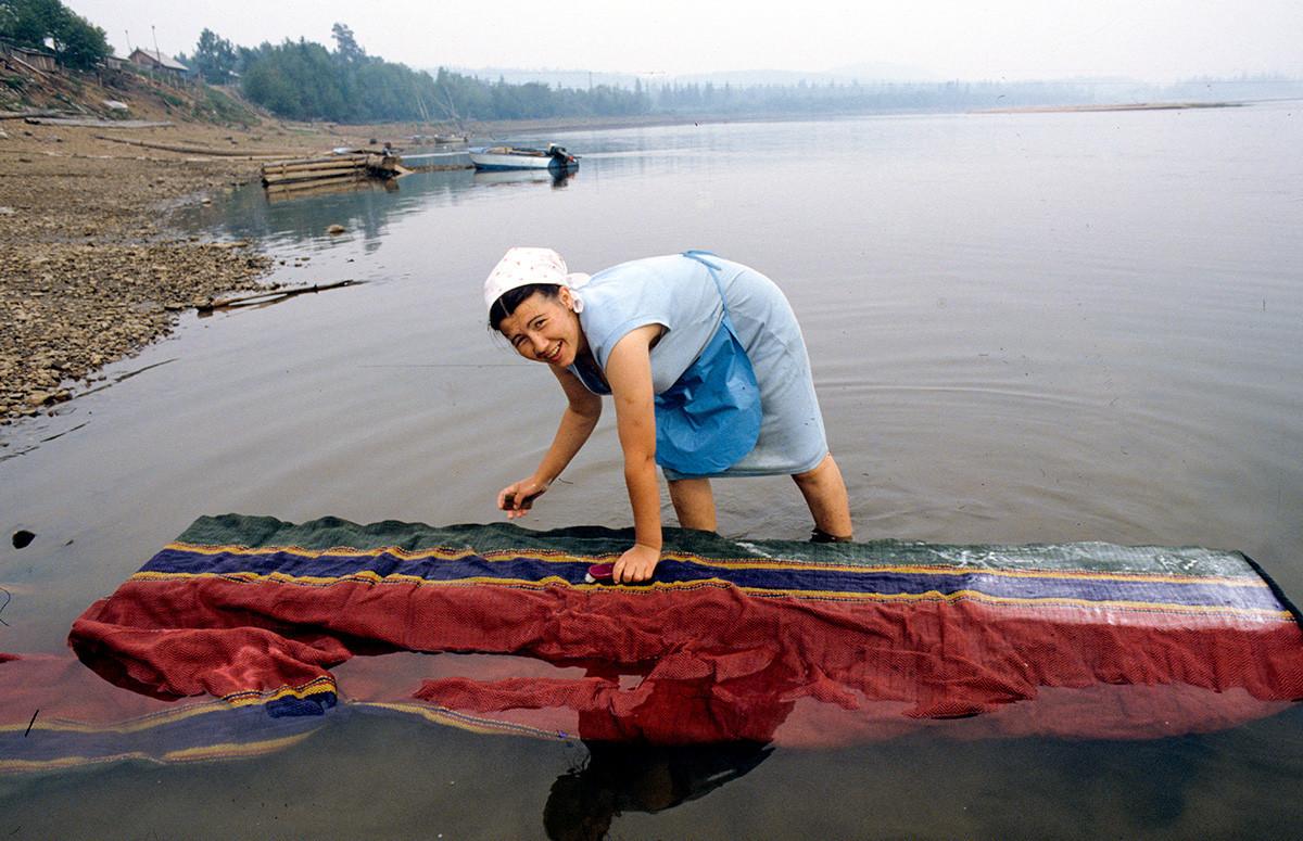 Prebivalka med pranjem preproge tekača na reki Birjusa na Krasnojarskem ozemlju.