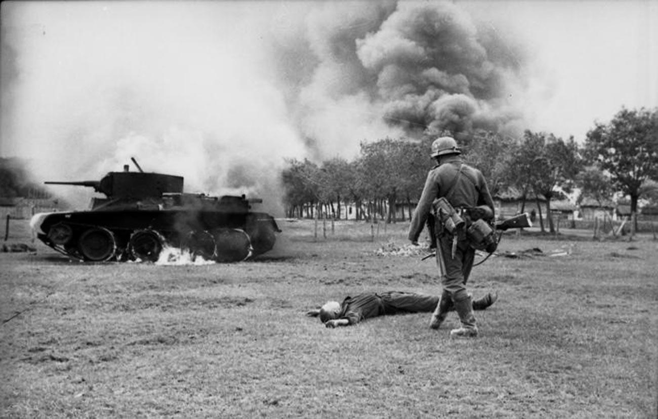 Soldat de l'infanterie allemande devant un conducteur de char soviétique tué et son char BT7 en flammes