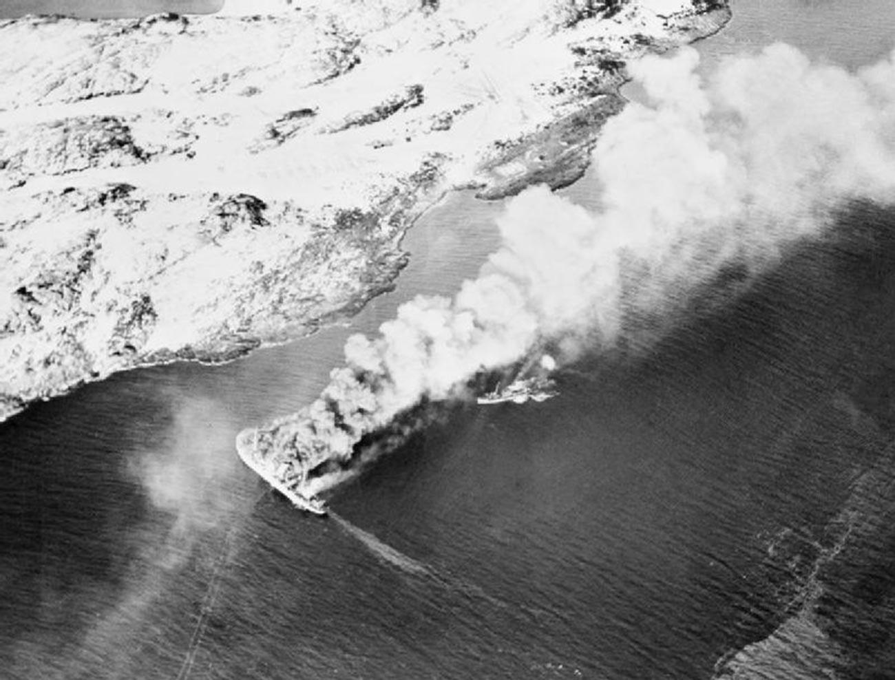 Товарниот брод Ригел кој беше во служба на германската армија и патролни чамци од него во пламен по бомбардирањето.
