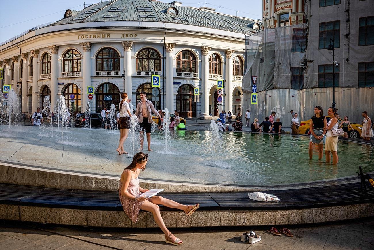 La gente si rinfresca in una fontana durante una calda giornata estiva nel centro di Mosca, 22 giugno 2021