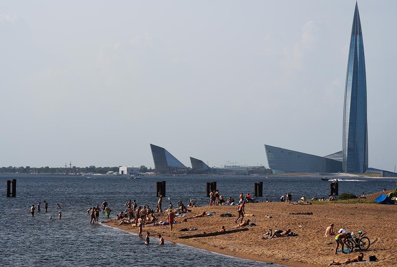 Люди на пляже на берегу Финского залива на Васильевском острове в Санкт-Петербурге.