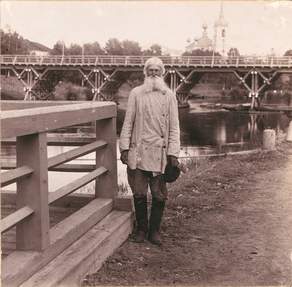 Vytegra. Local villager on background of Sivers Bridge & Resurrection Cathedral. Summer 1909