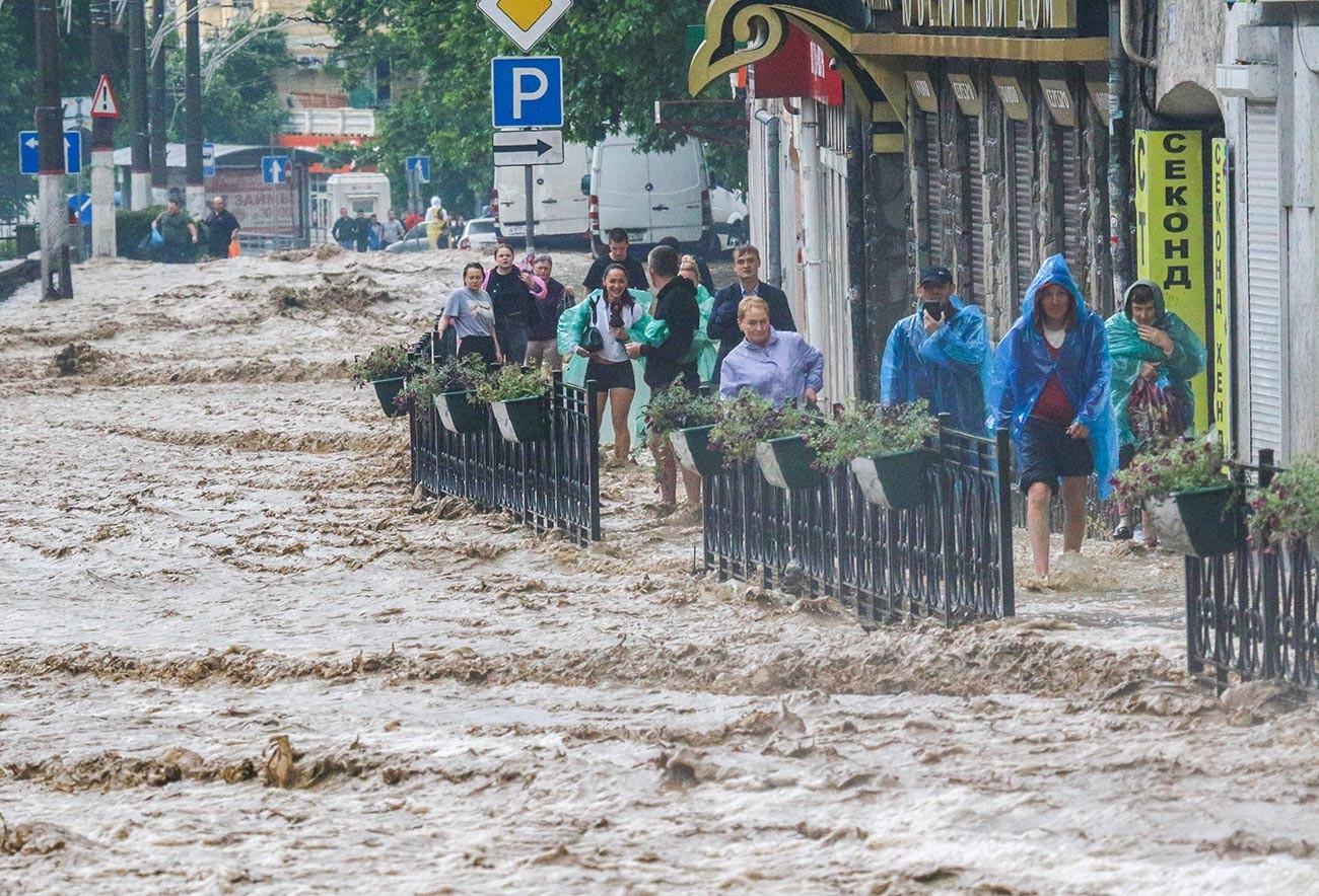 Хората на наводнена улица след обилните валежи в Ялта