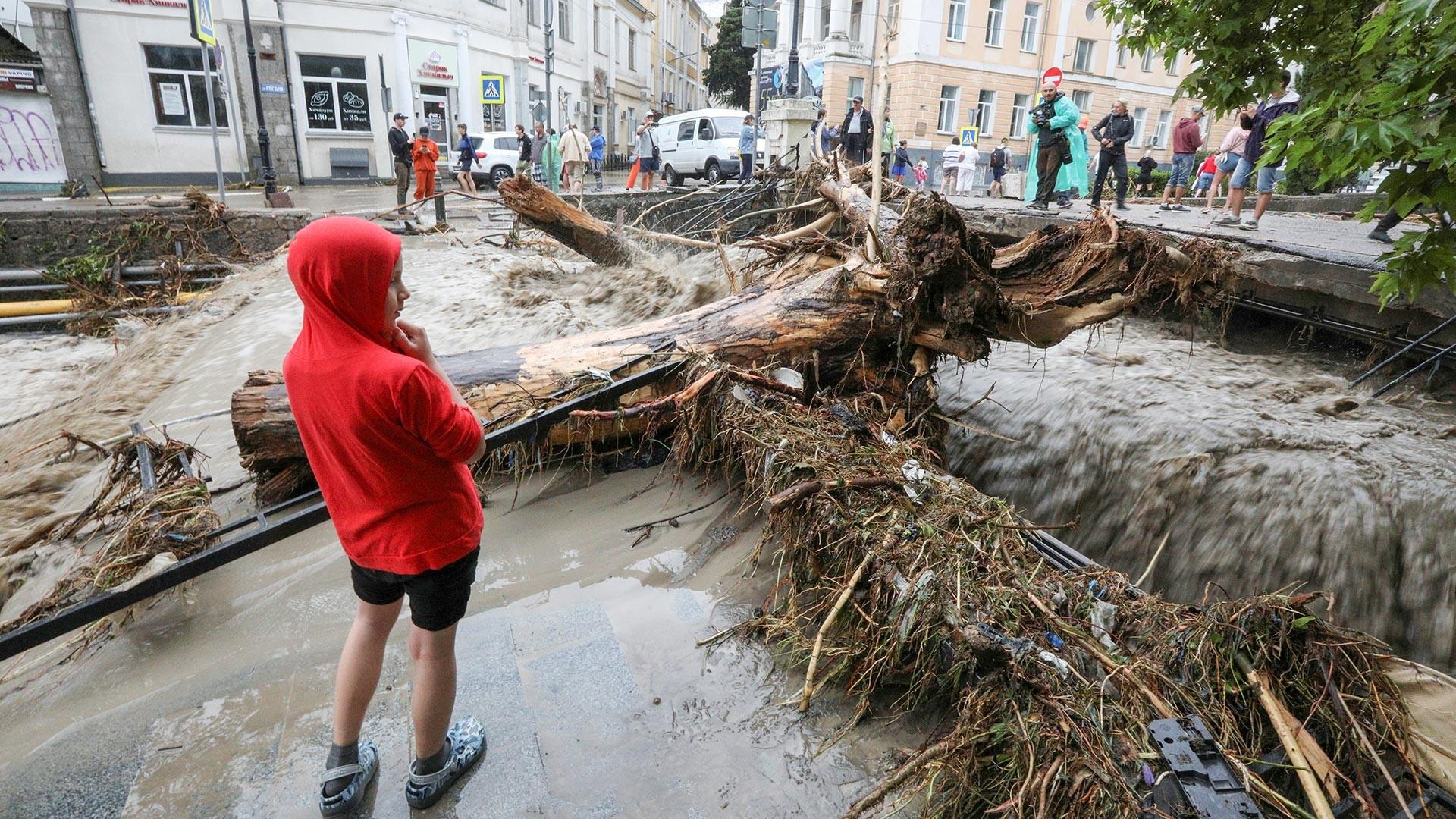 Хора на улица, засегната от наводненията в Ялта