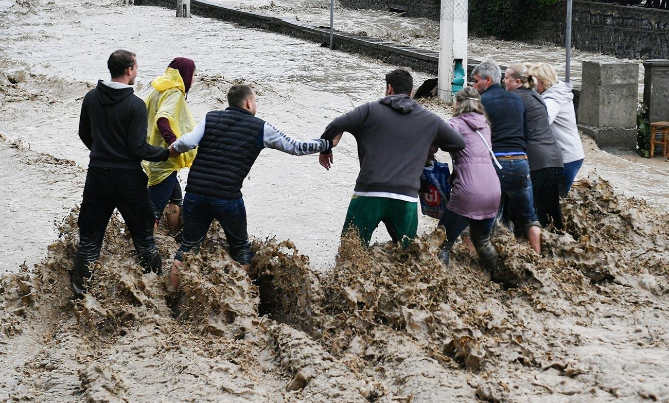 Луѓе си помагаат едни на други да поминат улица на Јалта. Крим го погодија обилни врнежи кои предизвикаа поплави.