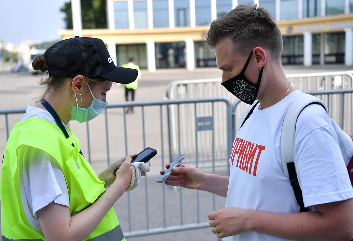 モスクワのルジニキ・スタジアムでUEFAユーロ2020のファンゾーン入り口の前にCOVID-19ステータスを証明するQRコードを提示する男性。Tシャツに「ワクチン接種を受けた」とプリントされている。