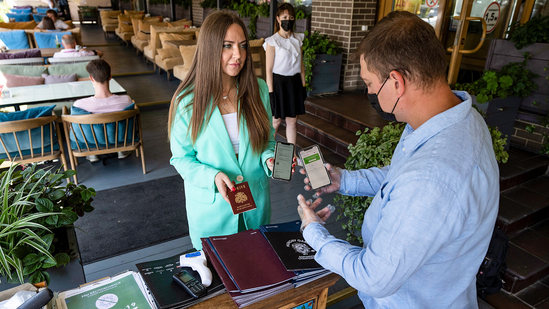 A restaurant employee checks a visitor's COVID-19 vaccination QR code at the entrance of a restaurant in Moscow, Russia, Tuesday, June 22, 2021. As proof of vaccination for entering a restaurant, customers must visit a government website and get a QR code.