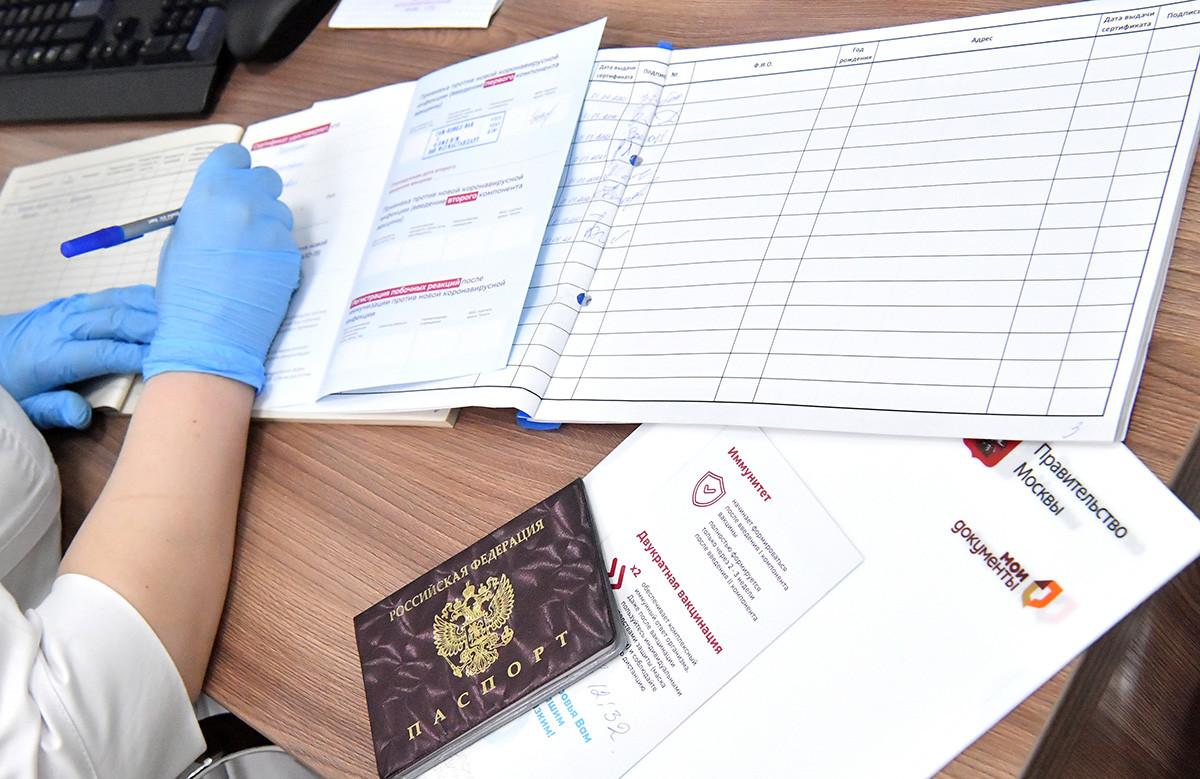 Медицинский работник заполняет сертификат о прививках в многофункциональном центре предоставления государственных и муниципальных услуг в Москве, Россия