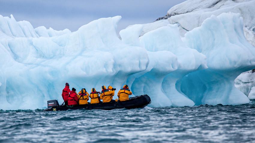 Operator tur 'Zodiak' membawa turis menggunakan perahu karet di depan gunung es di Samudra Arktik.