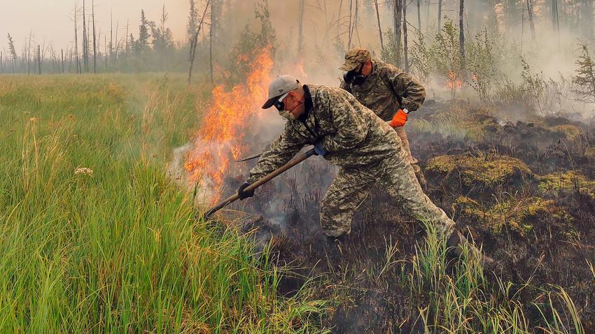 Voluntários apagam incêndio florestal na república da Iakútia, 17 de julho de 2021
