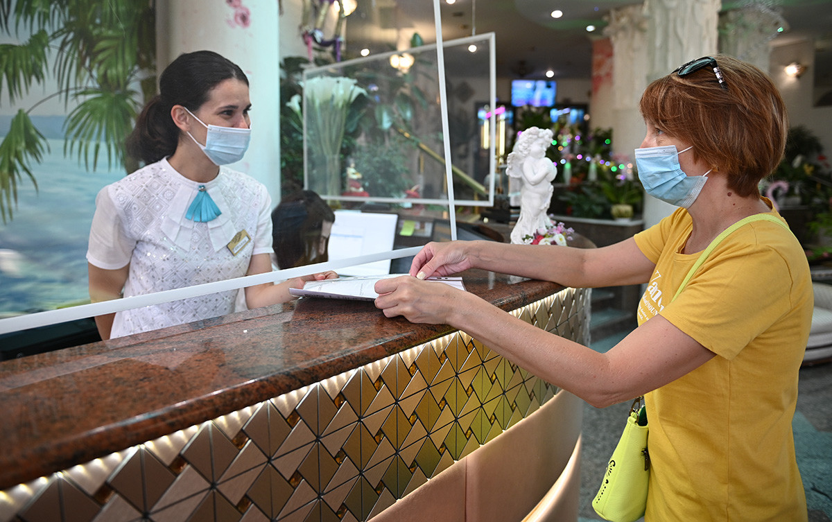 An employee of the sanatorium checks the certificate of vaccination against CoVID-19 from a guest before checking into the room of the sanatorium