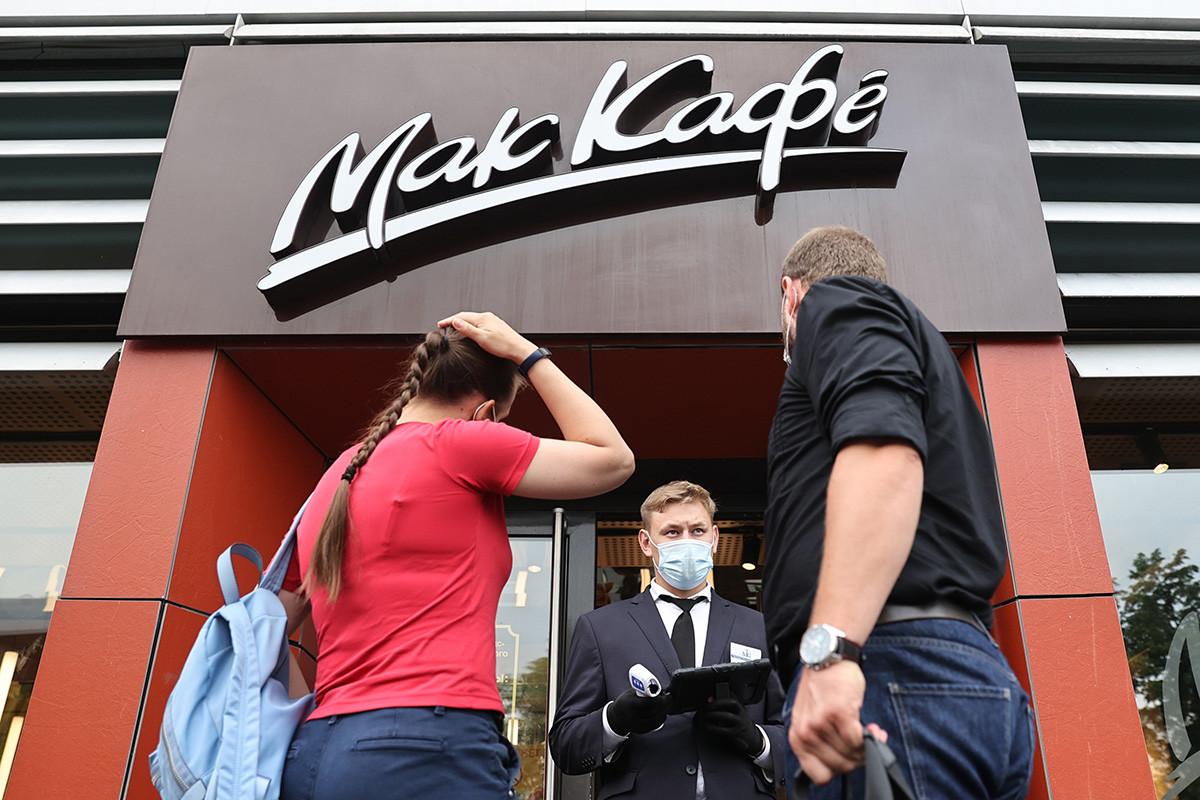 Orang-orang menunggu di luar restoran cepat saji McDonald's di Bolshaya Bronnaya ulitsa, Moskow. Mulai 28 Juni 2021, McDonald's memperkenalkan sistem nirsentuh untuk pesanan take-away dan mulai melayani pelanggan yang memiliki kode QR.