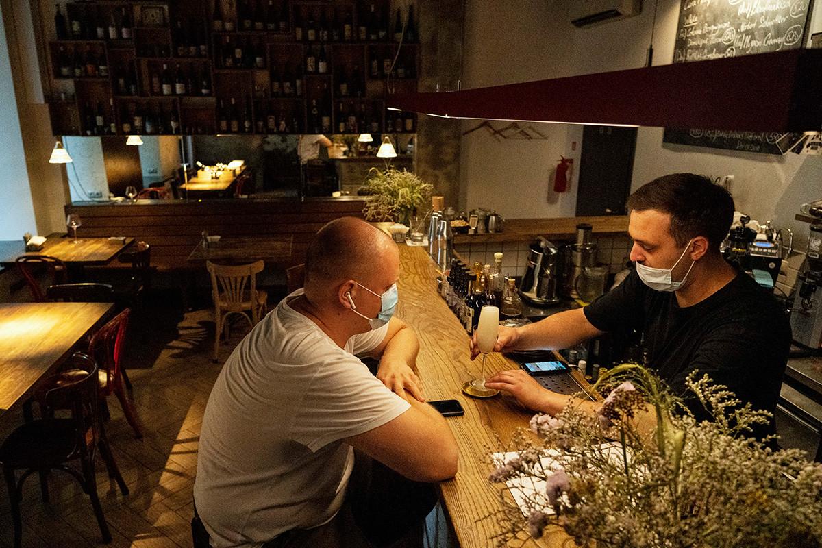 Seorang bartender menyajikan koktail di sebuah bar, Moskow, Senin (28/6). Biasanya, bar itu selalu ramai oleh pengunjung, tetapi ketika aturan kode QR di restoran dan kafe mulai berlaku, bar itu hampir kosong.