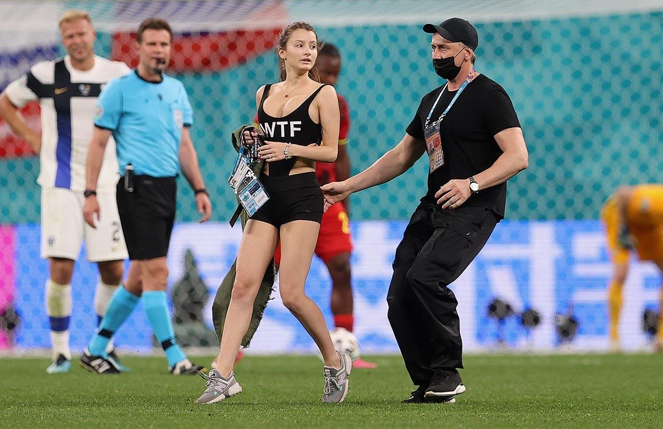 """Обезбеђење одводи са терена девојку која је усред утакмице групе Б Европског првенства 2020. године између Финске и Белгије на стадиону """"Санкт Петербург"""" 21. јуна 2021. утрчала на терен  због чега је на кратко прекинут меч."""