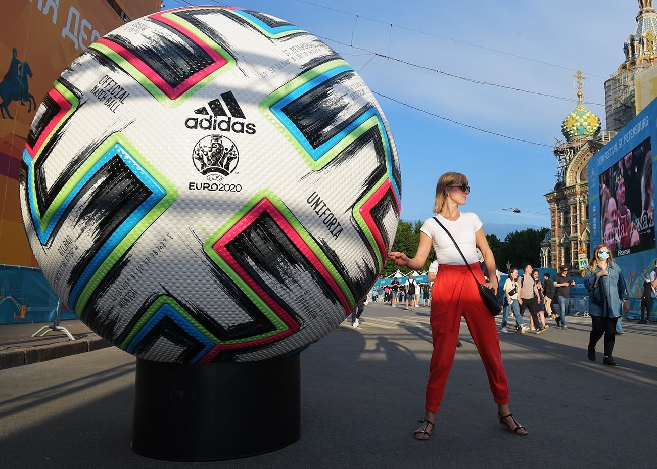 """Девојка се фотографира во близина на копија на официјалната топка на Европското фудбалско првенство 2020 во фан-зоната на плоштадот """"Коњушенаја"""" во Санкт Петербург."""