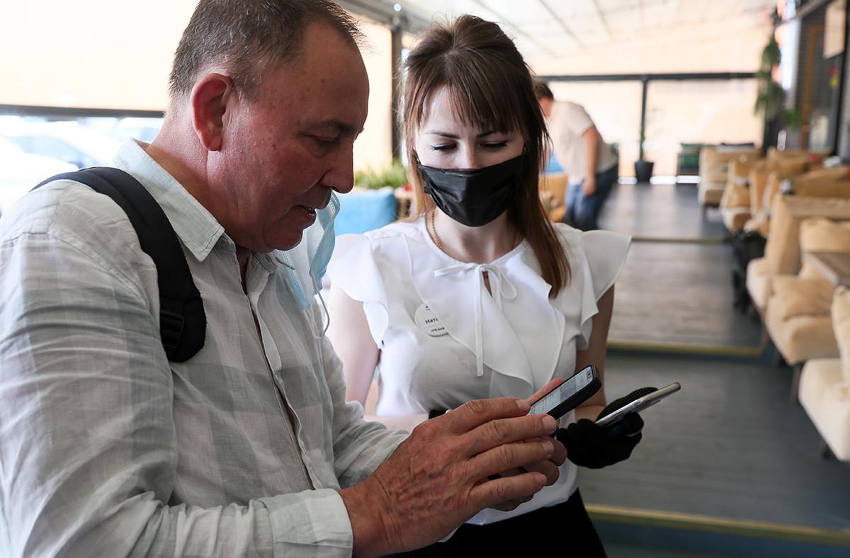Seorang pelayan dan pelanggan di restoran Chaikhona No. 1 yang mengikuti uji coba ruang bebas COVID-19 di Moskow.
