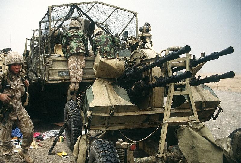Soldados británicos examinan el contenido de un camión de transporte iraquí en la autopista Basora-Kuwait, cerca de la ciudad de Kuwait, tras la retirada de las fuerzas iraquíes durante la operación Tormenta del Desierto (1991). Detrás del camión hay un cañón antiaéreo iraquí ZPU-4.