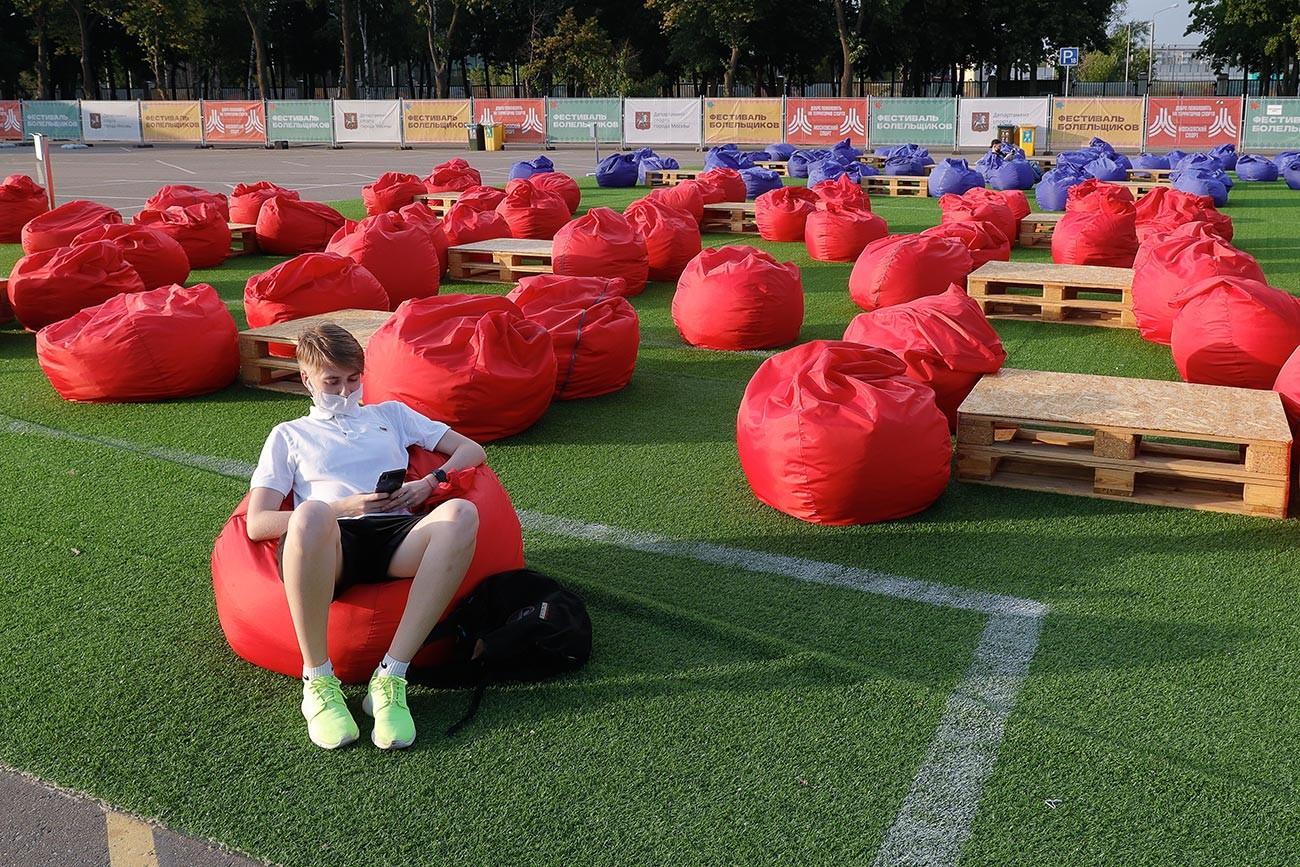 Seorang suporter bersantai sendirian di zona penggemar di Stadion Luzhniki, Moskow.