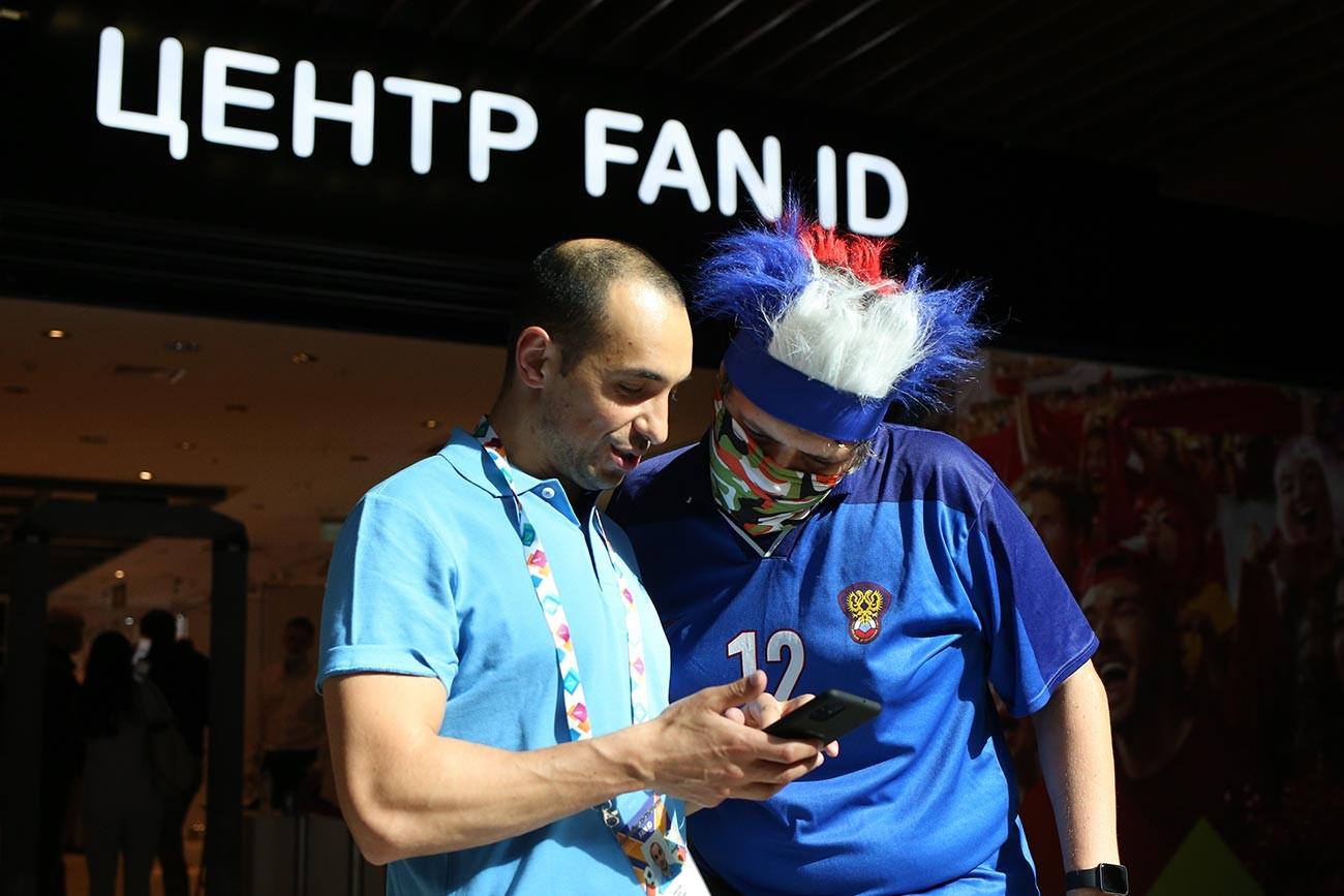Dua orang suporter di pusat penukaran Fan ID mengecek paspor sebelum turnamen Euro 2020 di pusat perbelanjaan Piterland.