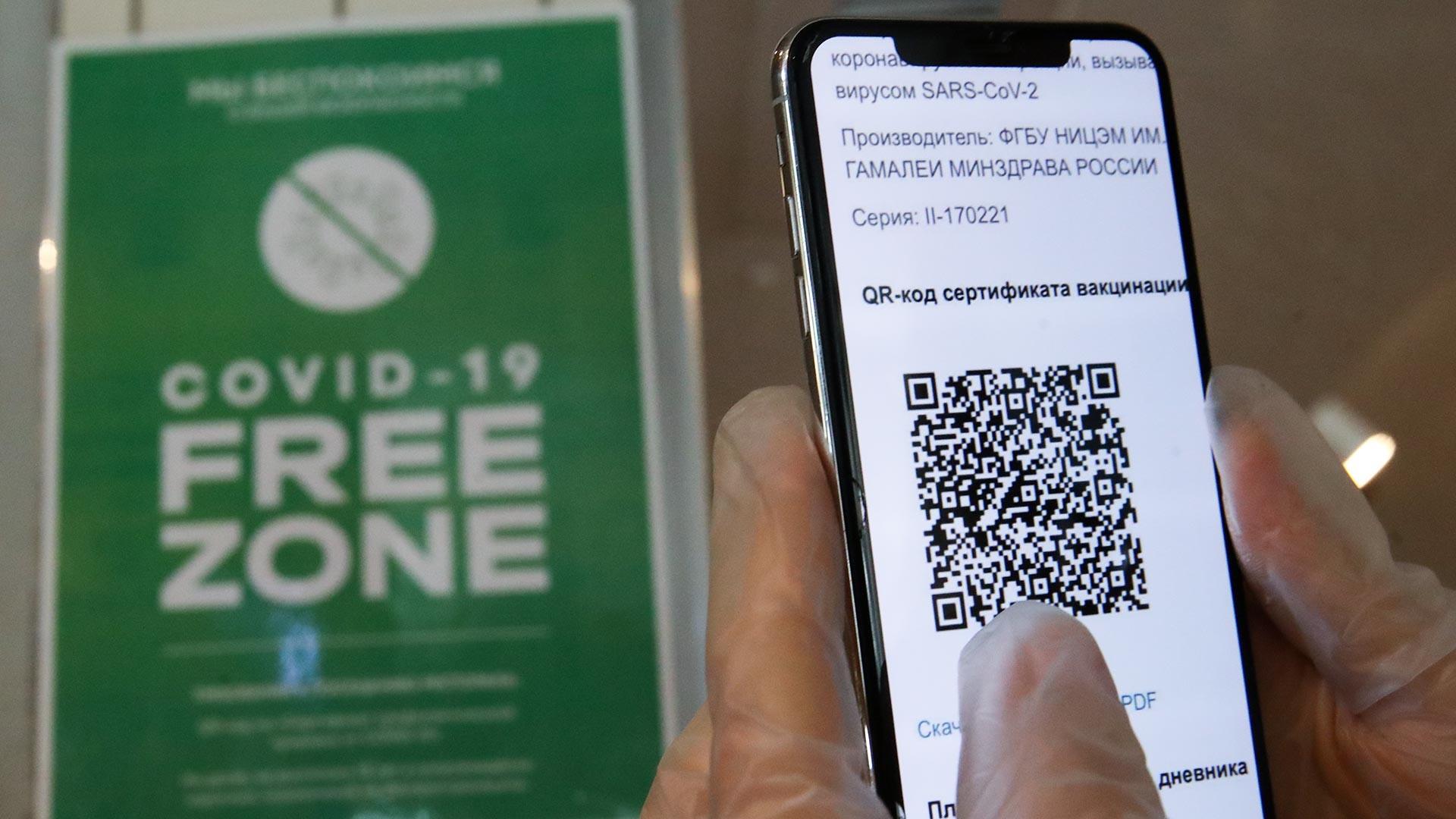 "Seseorang memegang ponsel yang menunjukkan kode QR di dekat tanda ""Zona Bebas COVID-19"" di pintu masuk restoran Mama Budet Rada bagi pelanggan yang telah mendapatkan vaksinasi di pusat kota Moskow."