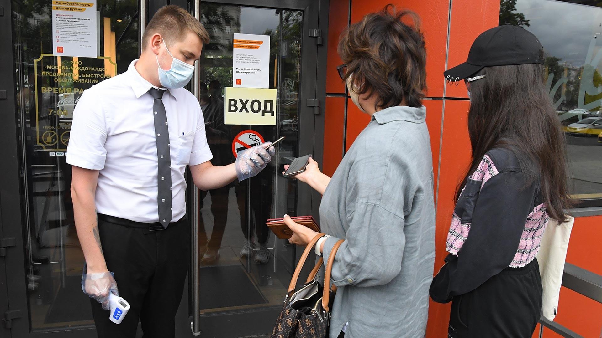 Clientes do McDonald's na praça Pushkinskaya, em Moscou, passam por verificação após novas medidas entrarem em vigor