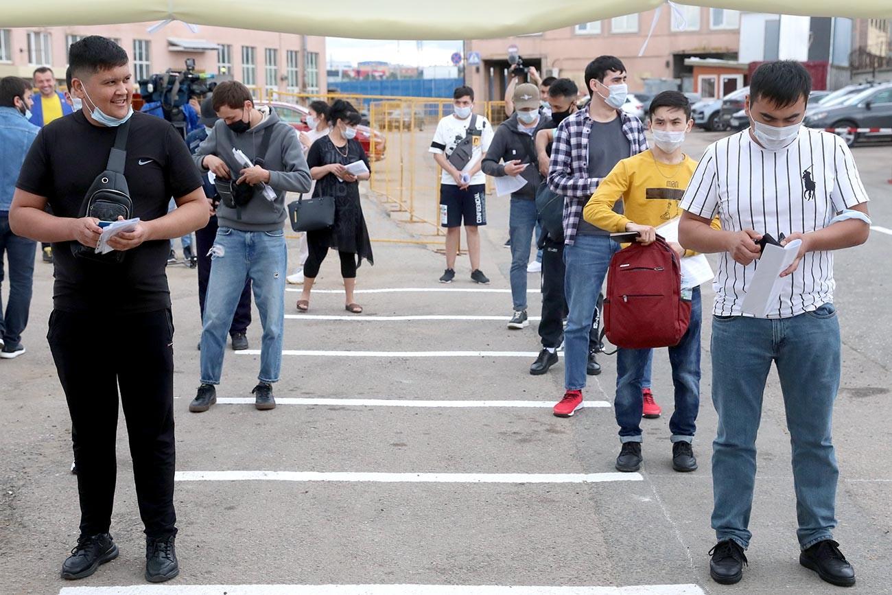 Imigrantes enfileirados para receber vacina no shopping Sadovod