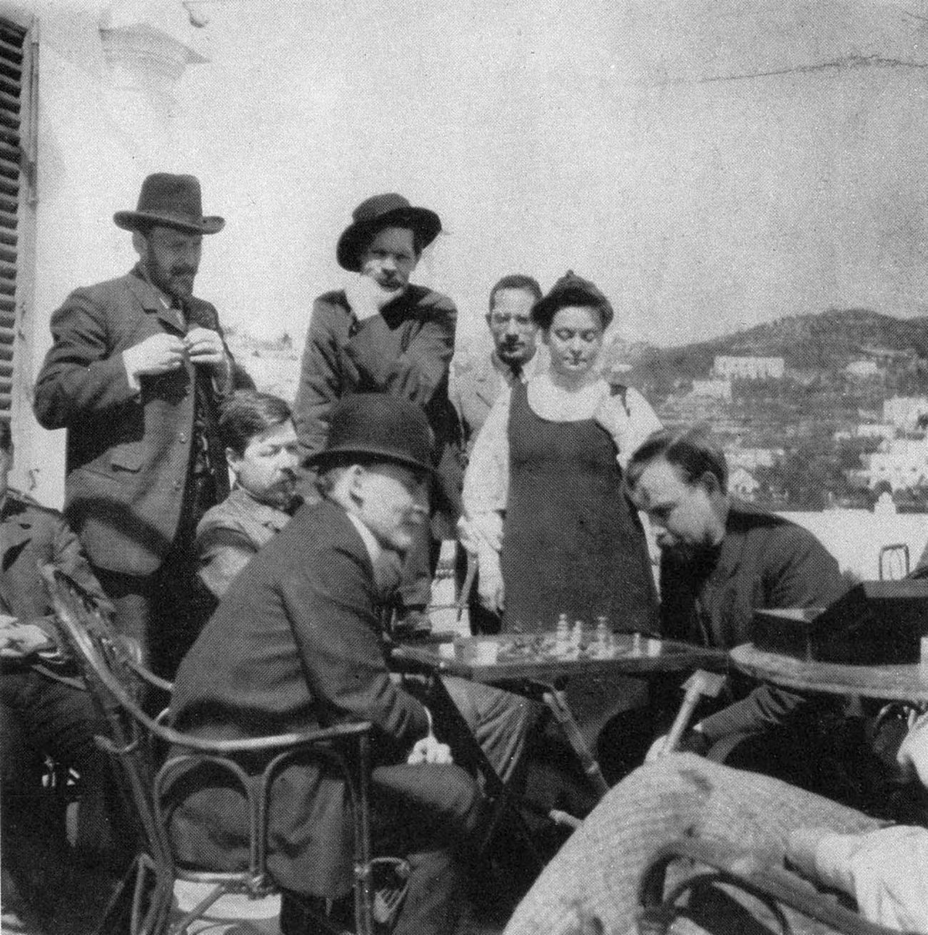 Vladimir Lenin plays chess with Alexander Bogdanov, 1908, Capri. Zinovy Peshkov is the second from the right in the top row, next to him is Maxim Gorky.