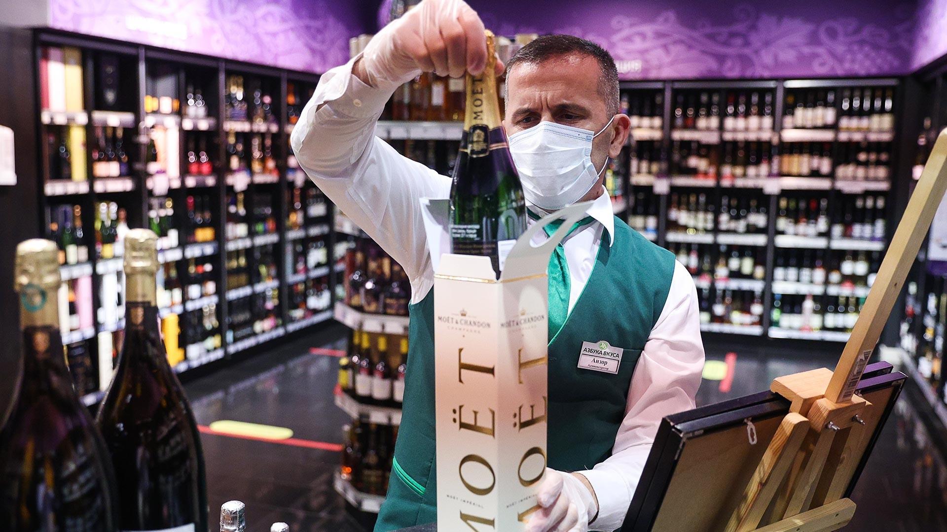 Служител на стелажа с пенливи вина Moet Hennessy в супермаркет