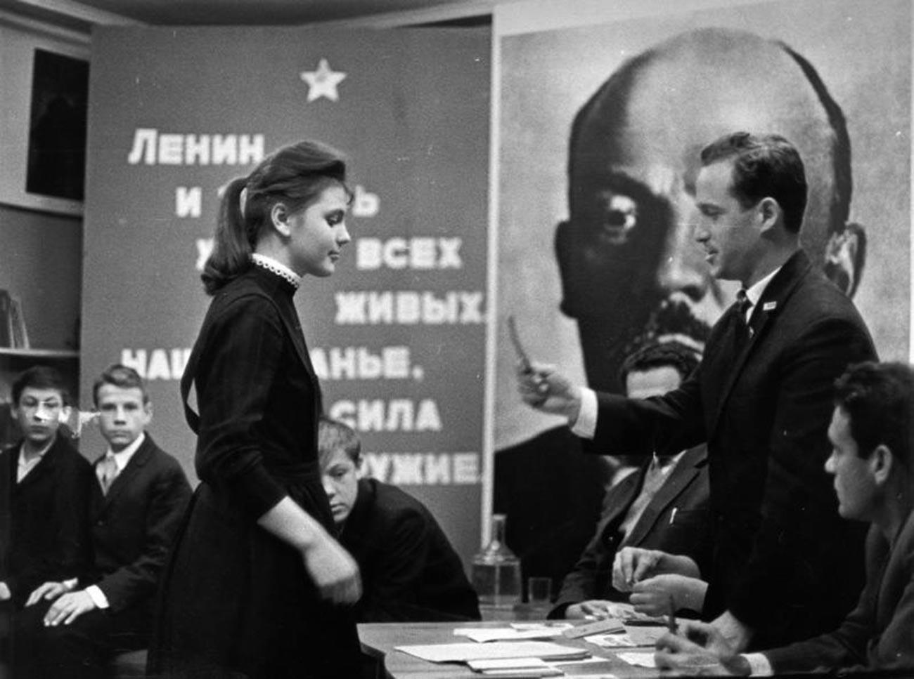 Seorang gadis menerima kartu keanggotaan Komsomol.