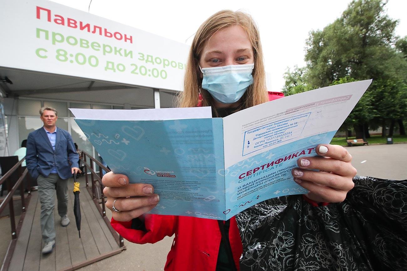 Jeune femme tenant son certificat de vaccination