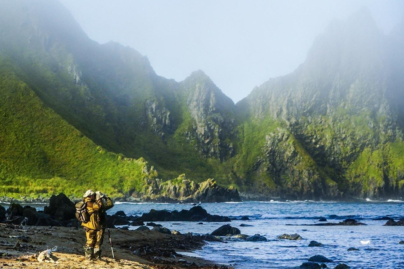 Членови на експедиција стојат на брегот на 'ртот Васин на островот Уруп (остров од јужната група на Големиот гребен на Курилските острови).