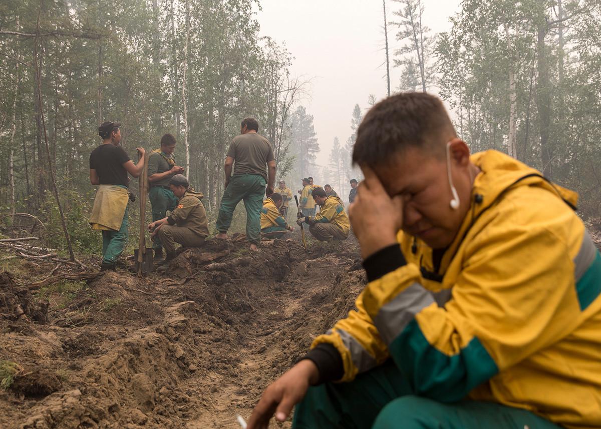 Employés du service iakoute de gestion forestière creusant une tranchée pour contrer l'avancée du feu, à proximité du village de Magaras