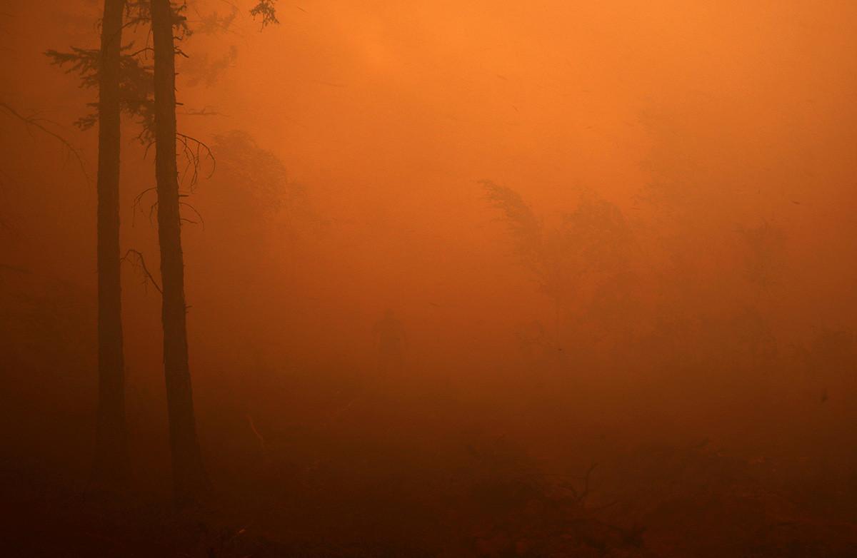 Bombeiro em operação para extinguir incêndio florestal perto da aldeia de Magaras, na região da Iakútia, 17 de julho de 2021