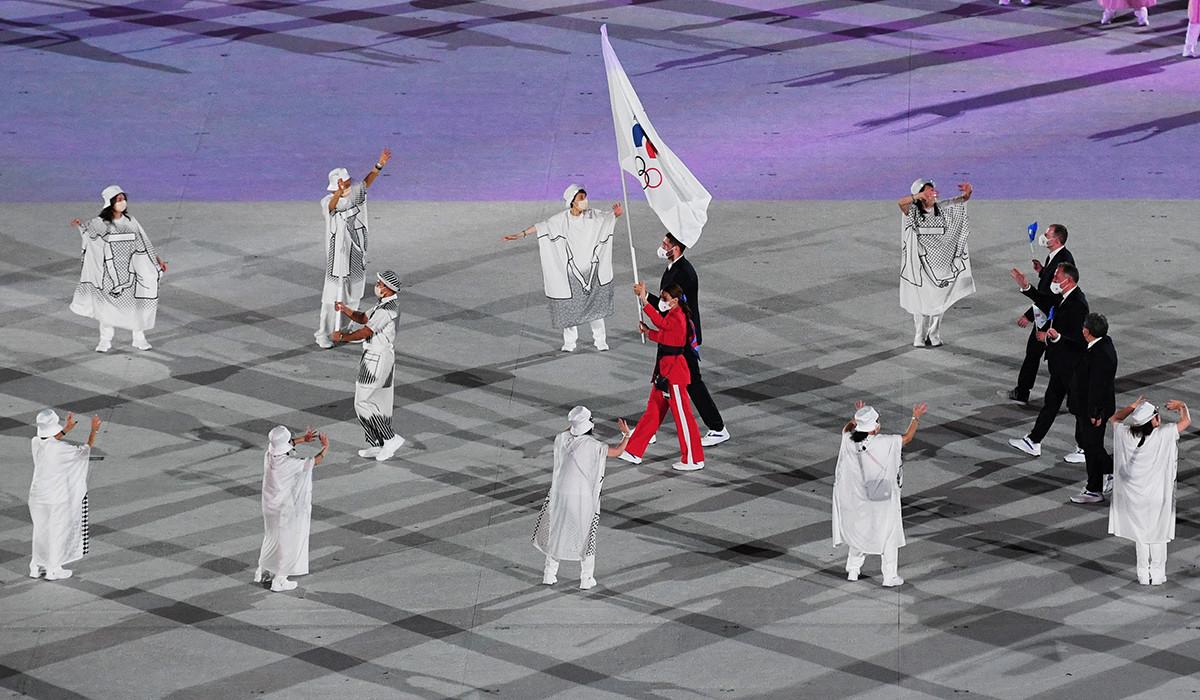Les porte-drapeaux de l'équipe du Comité olympique russe (COR), Sofia Velikaya et Maksim Mikhailov, défilent devant les athlètes lors de la cérémonie d'ouverture des XXXIIe Jeux olympiques d'été à Tokyo.