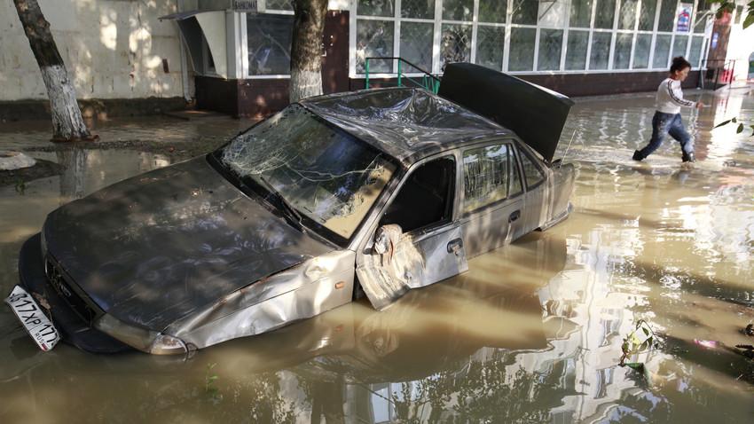 Seorang penduduk setempat melewati sebuah mobil rusak yang terjebak di jalan yang terendam banjir di Kota Krymsk, Krasnodarsky krai, Rusia.